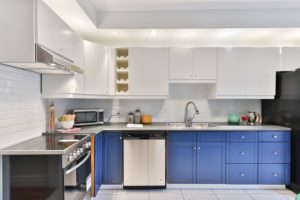 A kitchen designed with white cabinets and bright blue drawers.