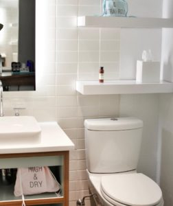 A small bathroom with wall shelves above the toilet